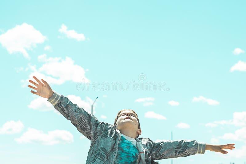 Kind mit den offenen Armen, die oben dem Himmel betrachten stockfotografie