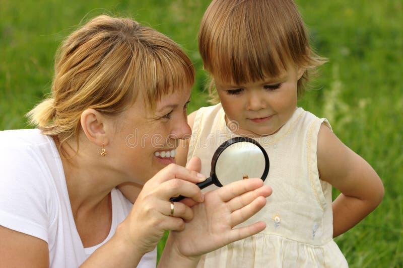 Kind mit der Mutter, die Schnecke betrachtet lizenzfreie stockfotos