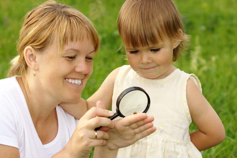 Kind mit der Mutter, die Schnecke betrachtet lizenzfreies stockbild