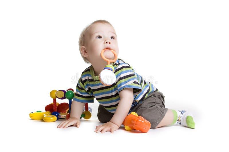 Kind mit einem Spielzeug im Mund stockfotografie
