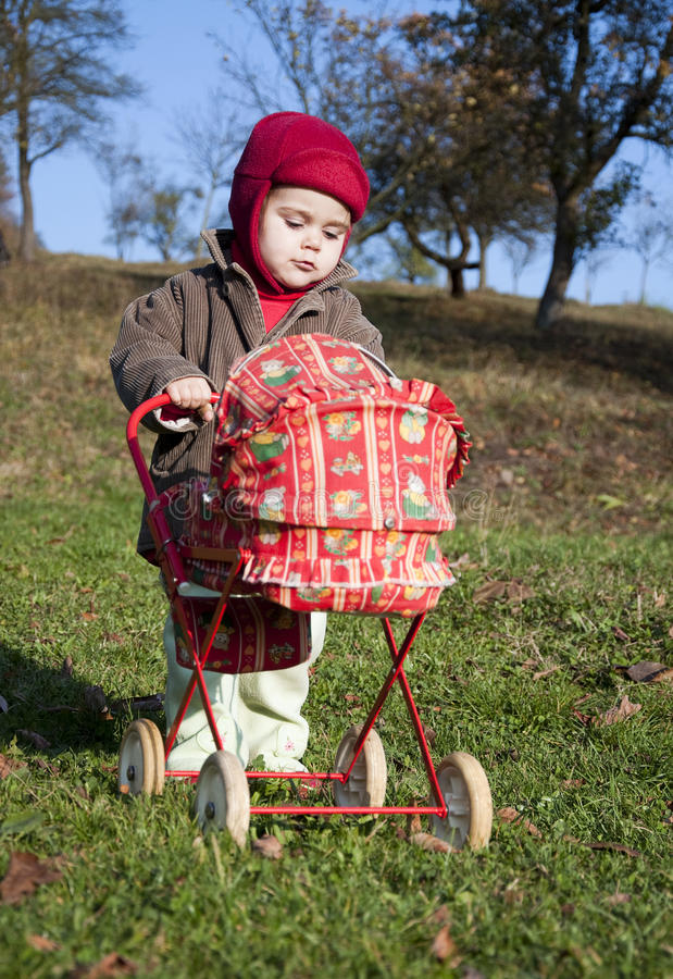 Kind mit einem Spielzeug Pram stockbilder