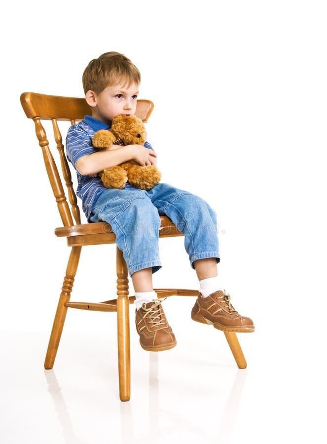 Kind mit einem Teddybären betreffen einen Stuhl lizenzfreie stockfotografie