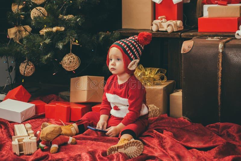 Kind mit einem Weihnachtsgeschenk auf hölzernem Hintergrund Glückliche Kinder schätzchen Enthält transparente Gegenstände Sankt K lizenzfreies stockbild