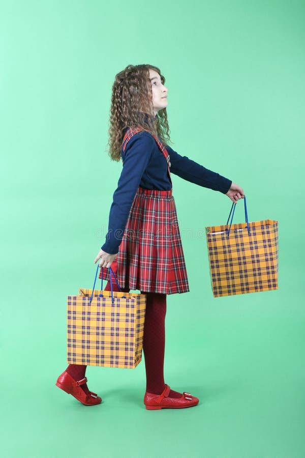 Kind mit einer gelben verpackenden karierten Beschaffenheit lokalisiert auf grünem Hintergrund Feiertagsgeschenk, Einkaufen stockfoto