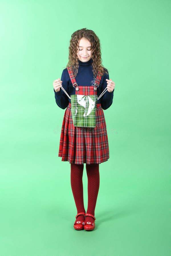 Kind mit einer grünen verpackenden karierten Beschaffenheit lokalisiert auf grünem Hintergrund M?dchen mag im Verkauf kaufen Jahr lizenzfreie stockbilder