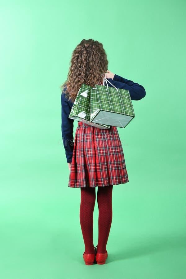 Kind mit einer grünen verpackenden karierten Beschaffenheit lokalisiert auf grünem Hintergrund M?dchen mag im Verkauf kaufen Jahr lizenzfreies stockfoto