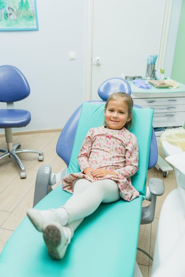Kind mit einer Mutter an einer Zahnarzt ` s Aufnahme Das Mädchen liegt im Stuhl, hinter ihrer Mutter Der Doktor arbeitet mit lizenzfreie stockbilder