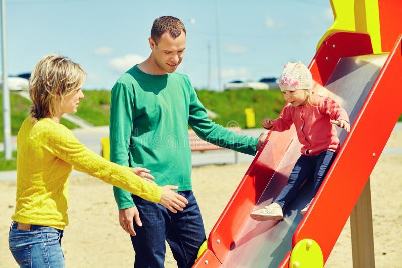 Kind mit Eltern an einem Spielplatz lizenzfreies stockfoto