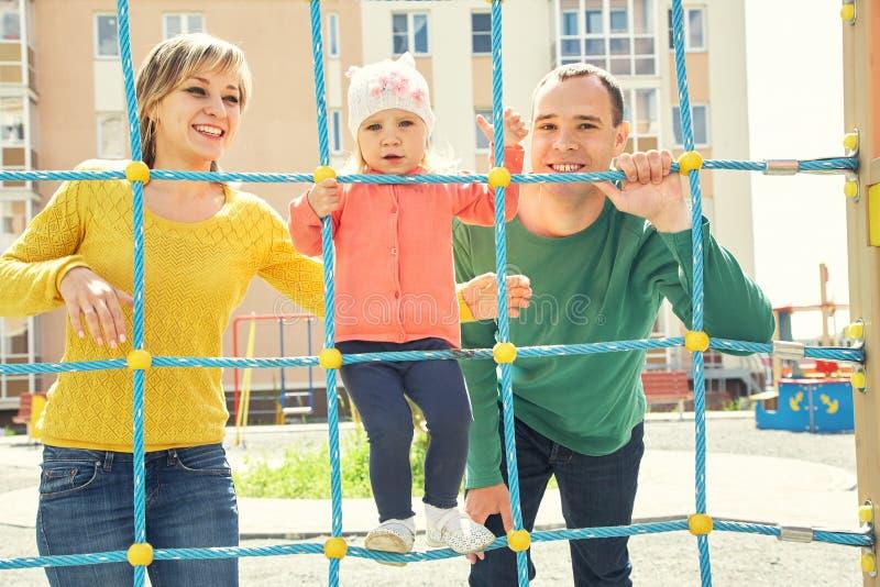 Kind mit Eltern am Spielplatz lizenzfreies stockfoto