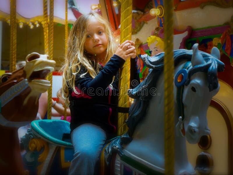 Kind mit gebohrtem Ausdruck auf Karnevals-Fahrt stockfoto