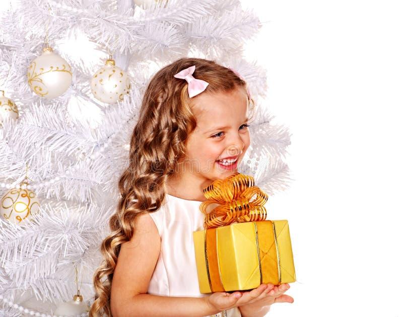 Kind mit Geschenkkasten nahe weißem Weihnachtsbaum stockfoto