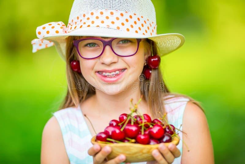 Kind mit Kirschen Kleines Mädchen mit frischen Kirschen Tragende Zahnklammern und -gläser des jungen netten kaukasischen blonden  lizenzfreie stockfotografie
