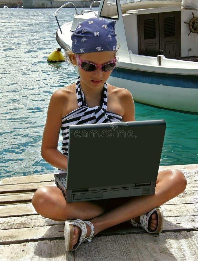 Kind mit Laptop im Hafen stockfotos