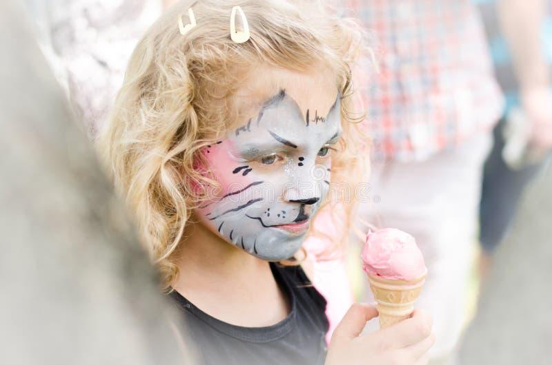 Kind mit Miezekatzegesichtmalerei und Eiscreme stockfotografie