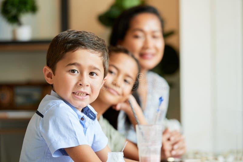 Kind mit Mutter und Schwester im Café lizenzfreie stockfotos