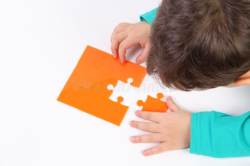 Kind mit Puzzlespiel stockfotos