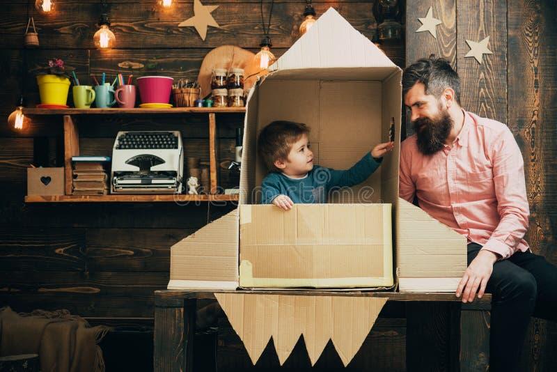 Kind mit Raketenrucksack täuschen vor, Kosmonaut zu sein Kind, das mit Vater spielt Glücklicher Vati und Sohn Erfolg, Führer und  lizenzfreies stockfoto