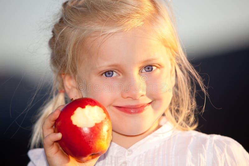 Kind mit rotem, süßem und gesundem Apfel stockfotografie