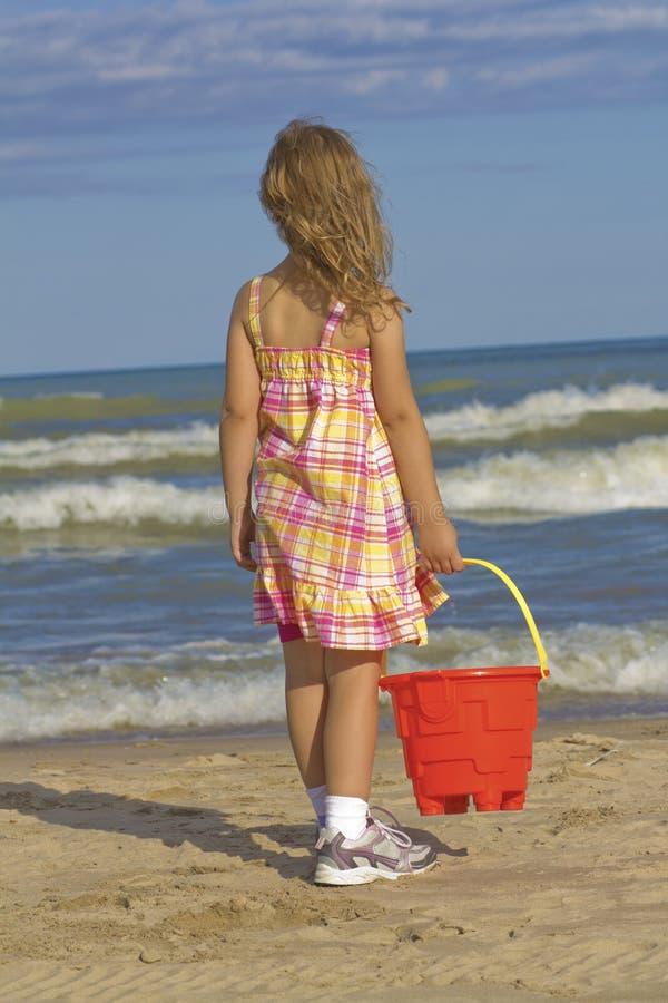 Kind mit Sandwanne am Strand lizenzfreie stockbilder
