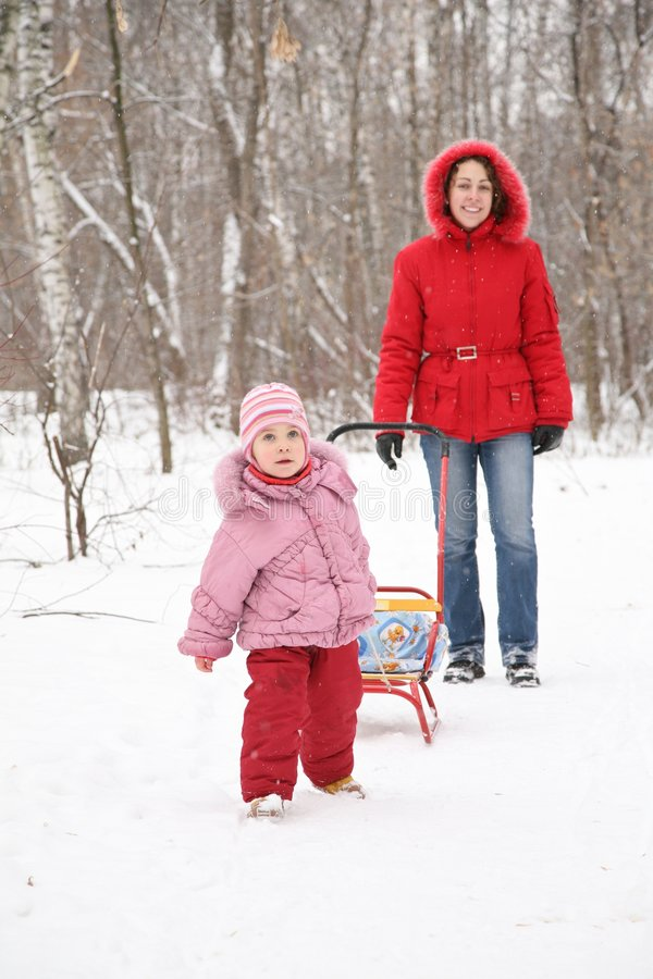 Kind mit Schlitten und Mutter an Winter 2 lizenzfreies stockbild