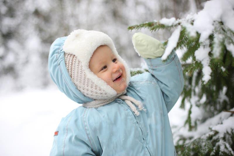 Kind mit schneebedecktem Zweig lizenzfreies stockbild