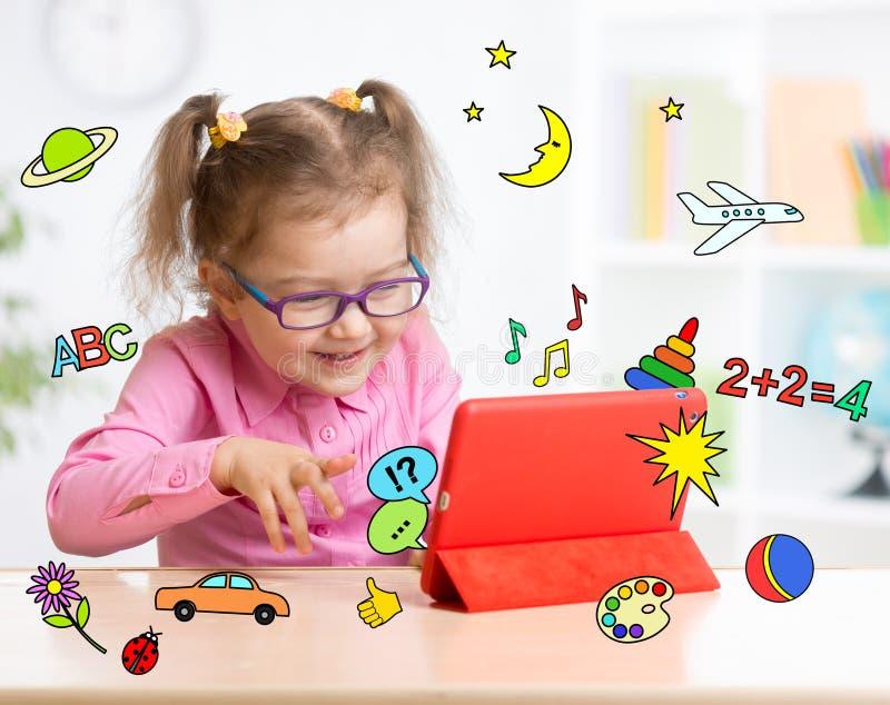 Kind mit Tablet-Computer in den Gläsern früh stockbilder