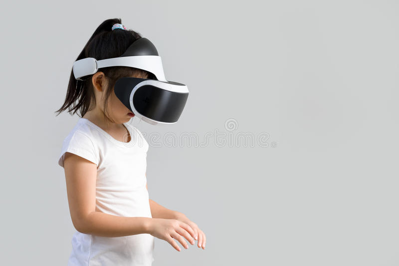 Kind mit virtueller Realität, VR, Kopfhörer-Atelieraufnahme lokalisiert auf weißem Hintergrund Kind, das virtuelle Welt Digital m stockfotografie