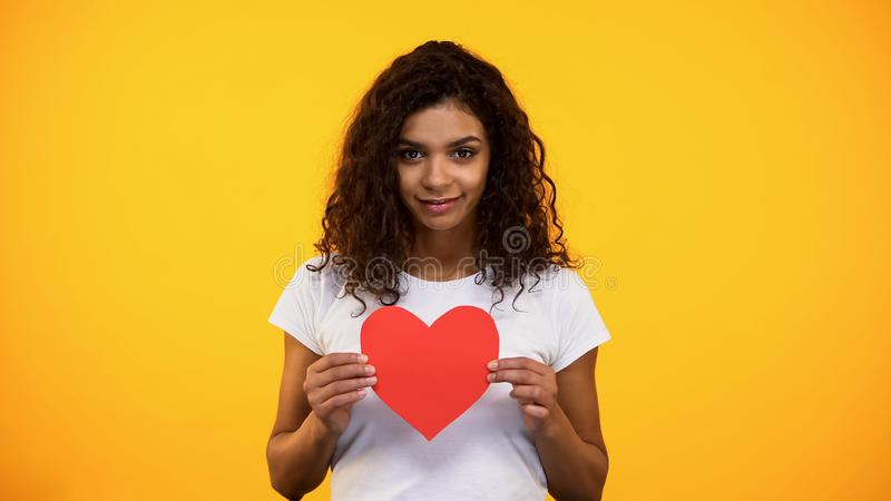 Kind mixed-race female showing red paper heart camera Valentines day, volunteer royalty free stock images