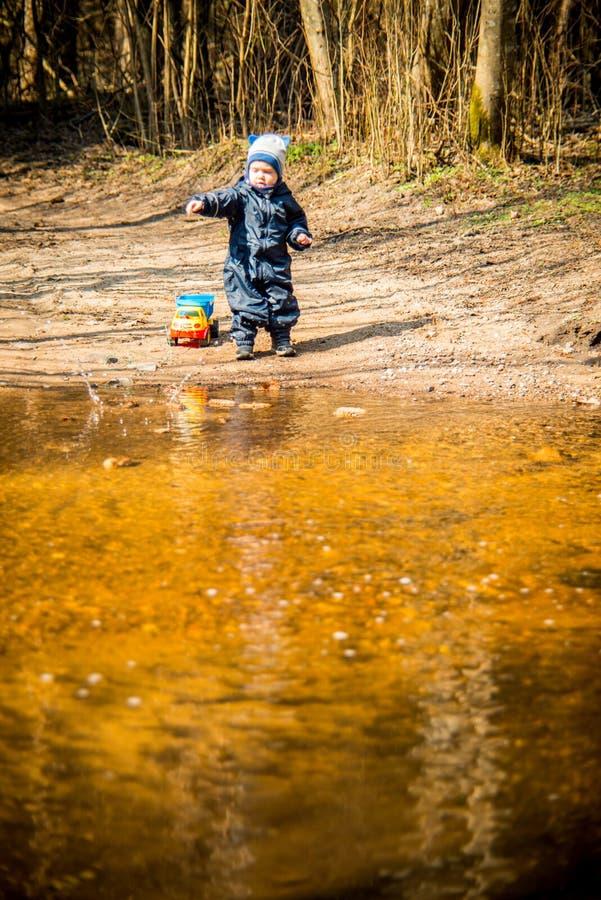 Kind nahe dem spielenden Wasser allein lizenzfreie stockbilder
