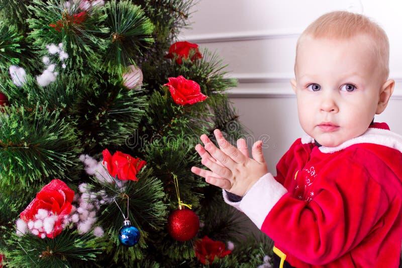 Kind nahe Weihnachtsbaum stockfotos
