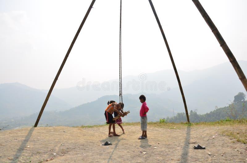 Kind Nepalese, der das Schwingen maschinell hergestellt für bamb spielt stockfotos