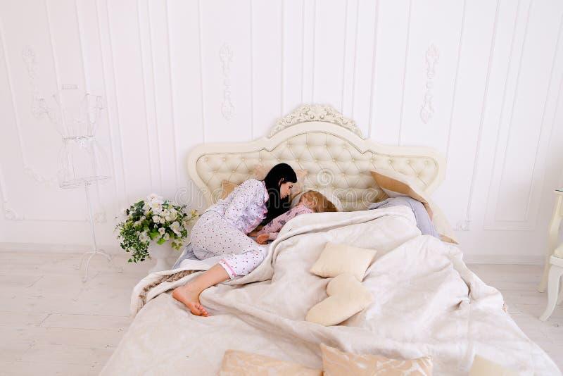 Kind nicht hören aber das Versuchen verbinden zu schlafen, liegend auf Bett im whi stockfotos