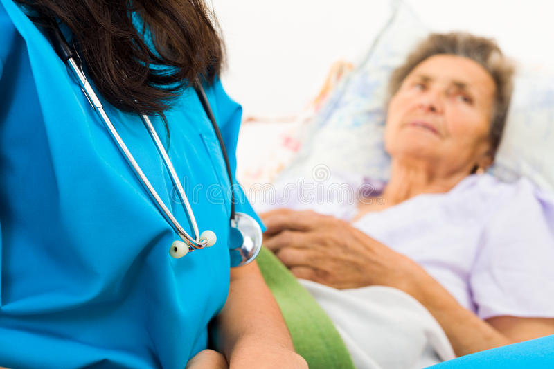 Kind Nurse with Elderly. Kind nurse easing elderly lady's days in nursing home with care help and joy stock photography