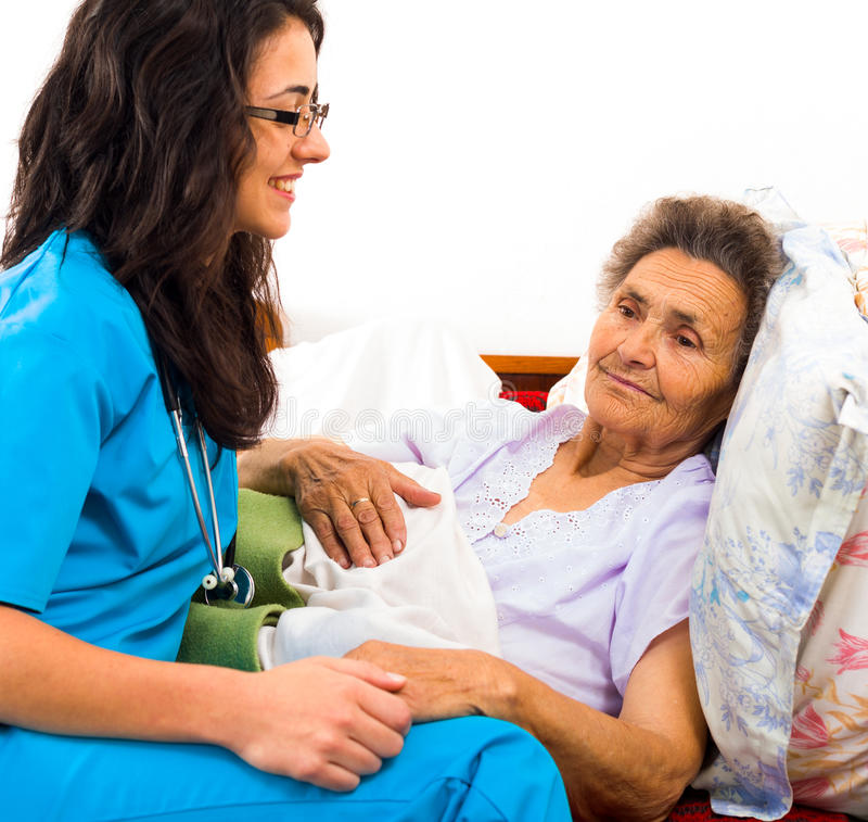 Kind Nurse with Elderly. Kind nurse easing elderly lady's days in nursing home with care help and joy stock photos