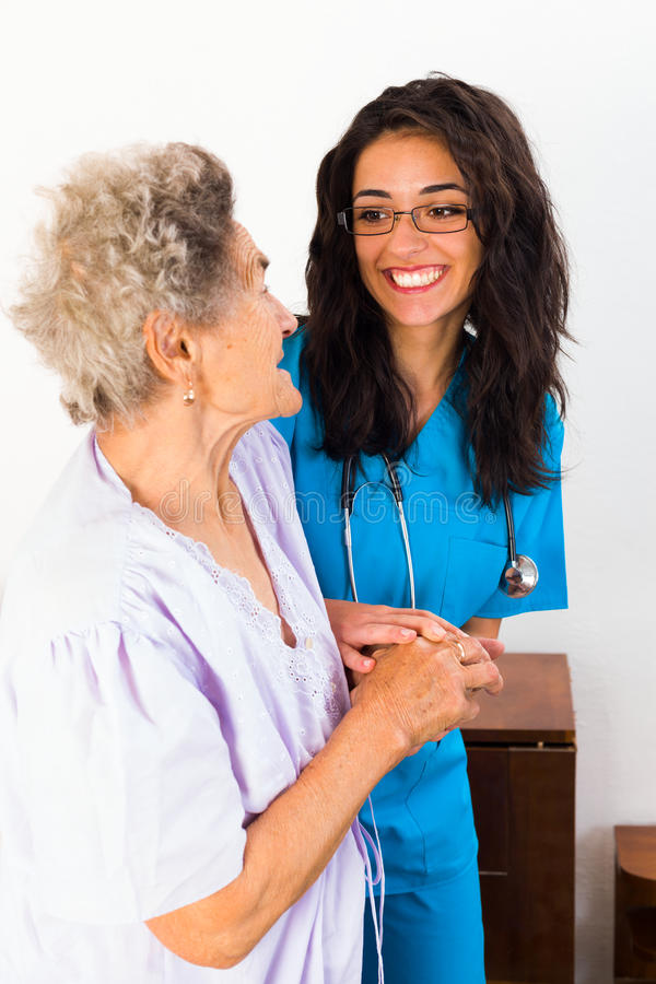 Kind Nurse with Elderly. Kind nurse easing elderly lady's days in nursing home with care help and joy royalty free stock photography