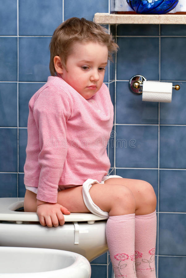 Kind op het toilet stock foto