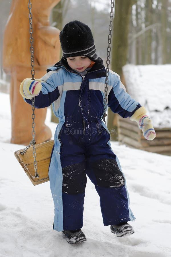 Kind op schommeling bij de winter stock afbeelding