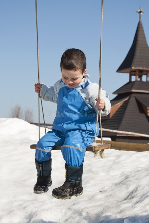 Kind op schommeling bij de winter stock fotografie