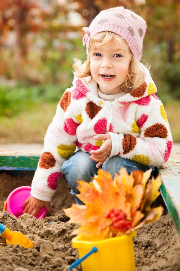 Kind op speelplaats in de herfst stock afbeelding