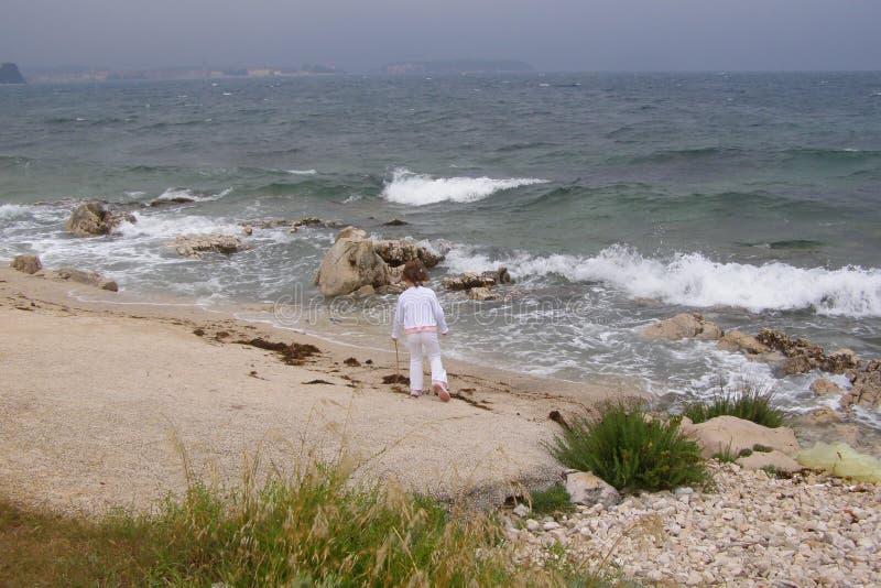 Kind op stormachtig strand stock fotografie