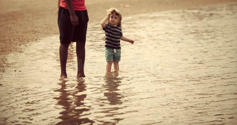 Kind op zee Kind onder volwassen supervisiegang in water op overzees strand stock foto