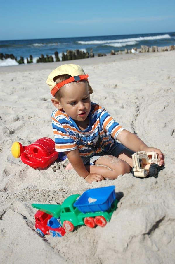 Kind playint mit Spielwaren auf dem Strand lizenzfreie stockbilder