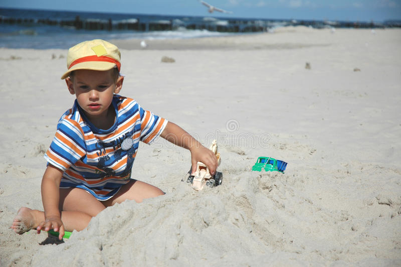 Kind playint mit Spielwaren auf dem Strand lizenzfreie stockfotografie