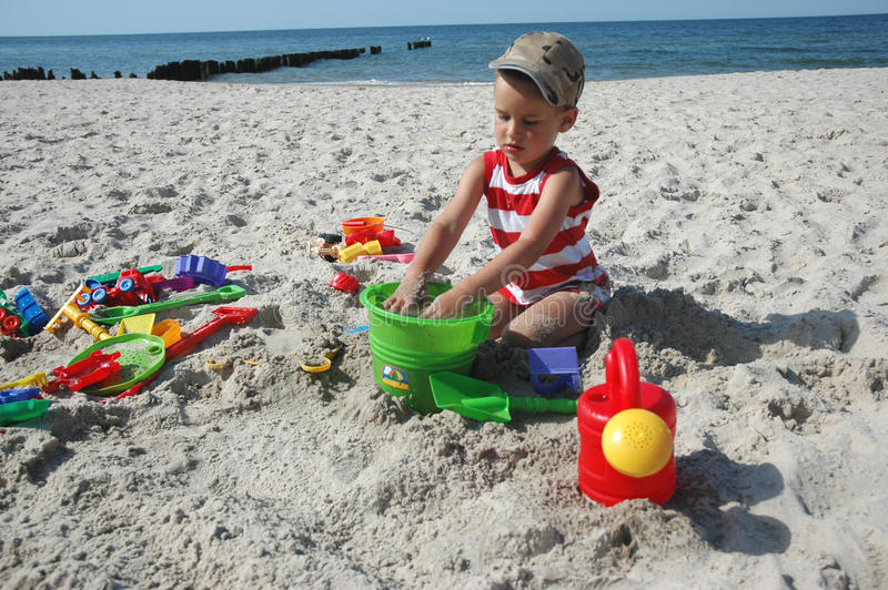 Kind playint mit Spielwaren auf dem Strand lizenzfreies stockbild