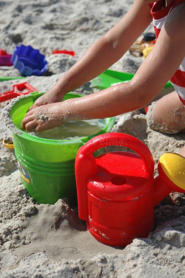 Kind playint mit Spielwaren auf dem Strand stockfotos