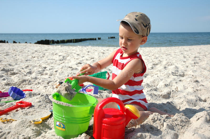 Kind playint mit Spielwaren auf dem Strand stockfoto