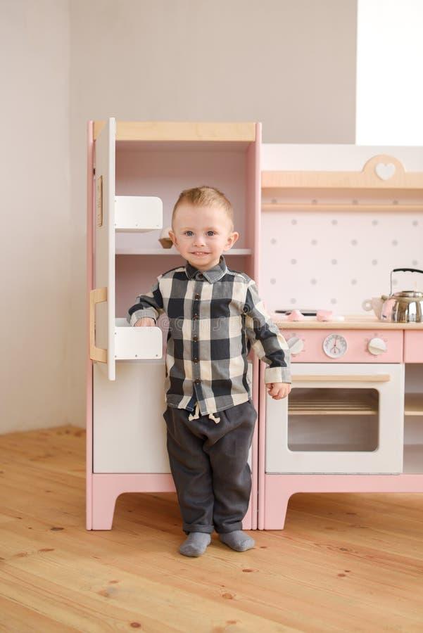 Kind in playroom concept Cute toddler boy glimlachen in houten speelgoedkeuken stock foto