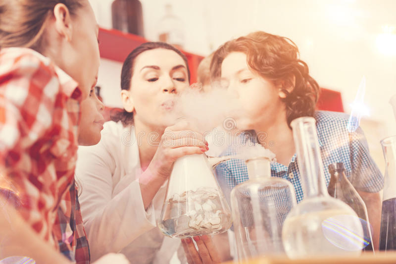 Kind pupils helping their analyst to finish experiment. Doing task. Delighted female person holding glass bottle and blowing on it while making smoke stock photo