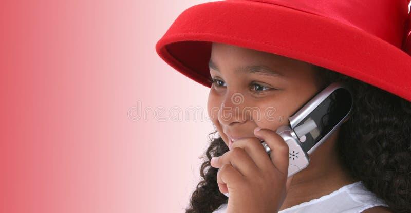 Kind in Red Hat dat op Cellphone spreekt royalty-vrije stock afbeelding