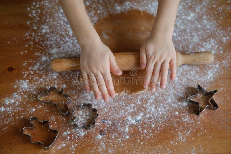 Kind rollt den Teig für Plätzchen stockbild